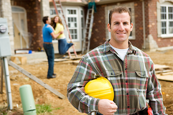 An image showing a happy construction worker with some happy excited new house owners in the background